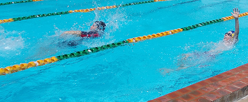 students competing in backstroke in the pool